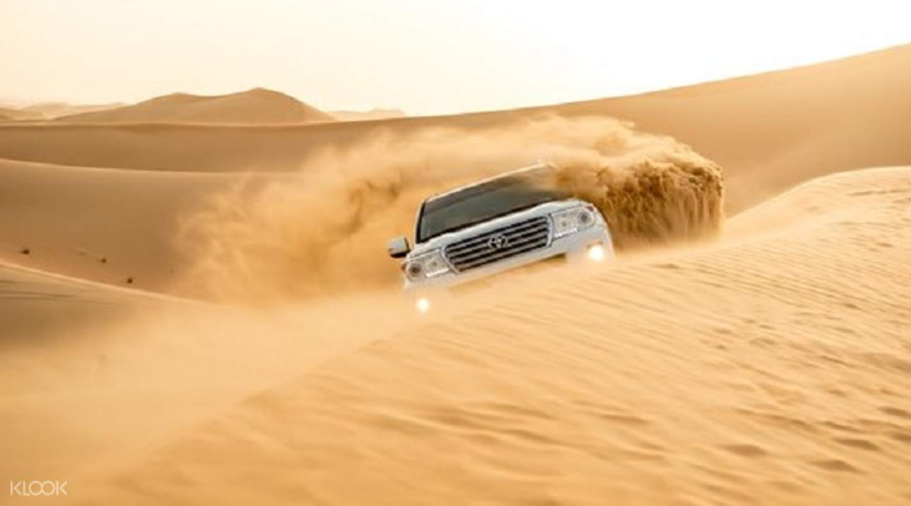 sand dunes with cars for dune bashing during the evening desert safari
